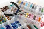 stock photo of beads  - An organizer full of multi colored beads and tools for making jewelry and crafts - JPG
