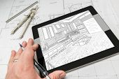 Hand of Architect on Computer Tablet Showing Custom Kitchen Illustration Over House Plans, Compass a poster
