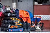 Постер, плакат: Protective Equipment For Motorsport With Spare Parts Stacked In A Van Background