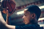 African American teenage boy concentrated on playing basketball poster