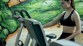 Young Attractive Woman Enhancing Her Endurance While Working Out On An Exercycle. Portrait Of A Beau poster