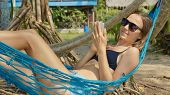 Young Happy Woman In Beachwear Lying On Hammock At The Sandy Beach And Using Smart Phone poster