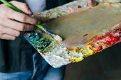 The Artist Holds A Palette With Paints And A Brush And Is Going To Paint On Canvas. A Man In Jeans A poster