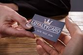 Human Hand Giving Loyalty Card To Another Person Over Wooden Desk poster