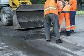 Workers On A Road Construction, Industry And Teamwork. Builders Workers At Asphalting Paver Machine  poster