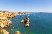 Scenic Cliffs And Grottos Explore By Tourists By Kayaks And Boats In Algarve, Portugal. Scenic Coast poster