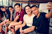 Group of young teenager friends on a basketball court relaxing taking a selfie poster