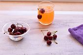 Fresh Delicious Red Cherry And Fresh Squeezed Orange Juice On Light Wooden Background. Fresh Ripe Ch poster