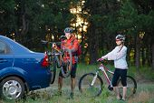 Young Couple Preparing for Riding the Mountain Bikes in the Forest. Unmounting the Bike from Bike Ra poster
