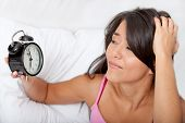 pic of late 20s  - Woman waking up and running late looking at the alarm clock - JPG