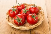 Red Tomatoes With Stems In Wicker Basket On Wooden Table poster