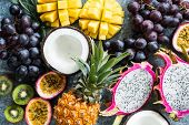 Assortment Of Exotic Tropical Fruits. Passionfruit, Dragonfruit, Mango, Pineapple, Kiwi, Grapes And  poster