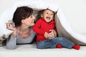 stock photo of babysitting  - Woman playing a hiding game with her child - JPG