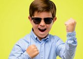 Handsome toddler child with green eyes happy and excited celebrating victory expressing big success, poster