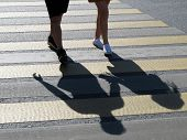 A Couple Crossing The Street At A Crosswalk. Female And Male Feet On A Pedestrian Crossing, Shadows  poster