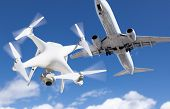 Unmanned Aircraft System Quadcopter Drone In The Air Too Close To Passenger Airplane. poster