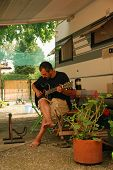 stock photo of campervan  - A barefooted guitarist practices under the awning of a motorhome - JPG