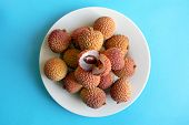 Lychee Fruit In White Plate On Blue Background, Top View. Many Fresh Lychees With One Opened In The  poster