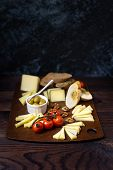 A Large Board With Sliced Different Types Of Cheeses With Olives, Cherry Tomatoes And Slices Of Garl poster