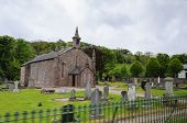 Country Stone Church In Carnlough Region Of Northern Ireland, Which Is Surrounded By Old Grave Stone poster