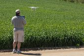 Pilot Flying Unmanned Aircraft Drone Gathering Data Over Country Farmland Field. poster