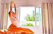 A Woman Stretches In The Morning In Her Bed. Enjoying The Morning In The Room. Morning Light In The  poster