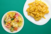 French Fries On A White Plate In The Green Background. French Fries With Vegetable Salad Fast Food T poster