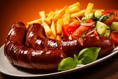 stock photo of sausage  - Grilled sausages with chips and vegetables - JPG