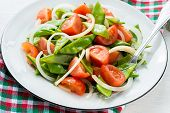 stock photo of snow peas  - Fresh snow peas and tomato salad on plate selective focus - JPG