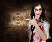 image of gruesome  - Terrifying marketing woman promoting dead space when pointing to grunge wallpaper inside a haunted house in a depiction of halloween advertising - JPG