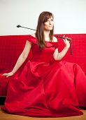 stock photo of riding-crop  - beautiful woman in a red ball gown sitting on a red couch and holding a riding crop - JPG