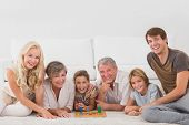 Family looking at the camera with board games in sitting room
