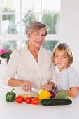 Granny cutting vegetables with her grandson in kitchen