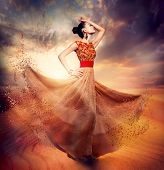 Dancing Fashion Woman wearing Blowing Long Chiffon Dress. Fashion Art Fantasy Collage. Sand Fairy
