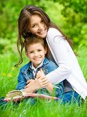 stock photo of mums  - Mum and son with book sitting on green grass in green park - JPG