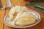 stock photo of biscuits  - Fresh baked biscuits with country gravy on a rustic wooden table - JPG