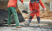 stock photo of reconstruction  - builders workers at asphalting paver machine during Road street repairing works - JPG