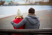 stock photo of bench  - Back view of affectionate couple sitting on the bench and looking at river - JPG