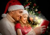 family, christmas, x-mas, winter, happiness and people concept - smiling father and daughter in sant