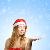 Young Woman In Santa Hat With Open Hand