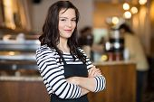 Portrait of pretty young waitress standing arms crossed in cafeteria