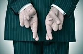 picture of fingers crossed  - a man wearing a suit crossing his fingers in his back - JPG