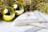 foto of christmas dinner  - Shiny golden color Christmas New Year decoration ornament balls with textured fabric napkins on a table - JPG