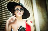 pic of brunette  - Attractive brunette girl with black hat, red scarf and sunglasses posing outdoor. Beautiful fashionable young woman with modern accessories, urban shot. Gorgeous brunette with large black hat smiling.