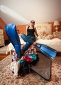stock photo of flipper  - Dreamy woman in flippers holding legs on suitcase at bedroom - JPG