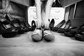 image of flat-foot  - Black and white photo of woman holding ballet flats rather then high heels - JPG