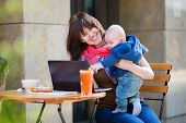 pic of internet-cafe  - Young mother with little son working on her laptop in a cafe - JPG