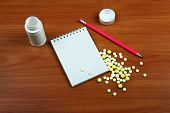 picture of home remedy  - Writing Pad and the Pills on the Wooden Table closeup - JPG