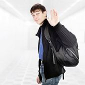 stock photo of knapsack  - Teenager with Knapsack wave Goodbye in the White Corridor - JPG