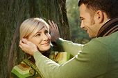 picture of caress  - Caucasian boyfriend caressing happy romantic blond lady leaning against tree at forest - JPG